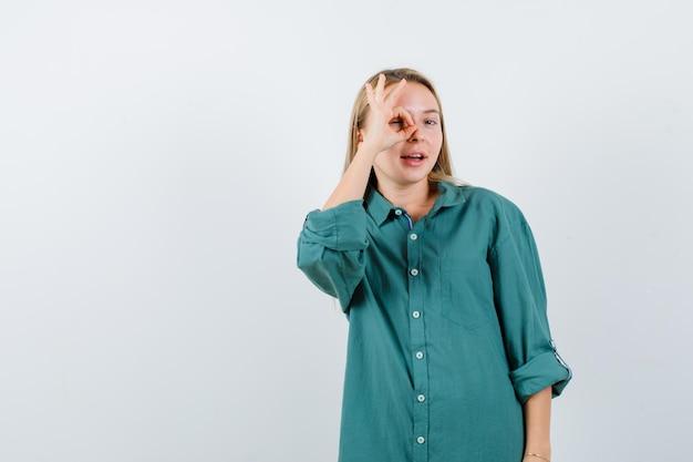 Młoda dama pokazując znak ok na oko w zielonej koszuli i patrząc wesoło.