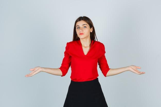 Młoda dama pokazująca bezradny gest w czerwonej bluzce, czarnej spódnicy i zdziwiona