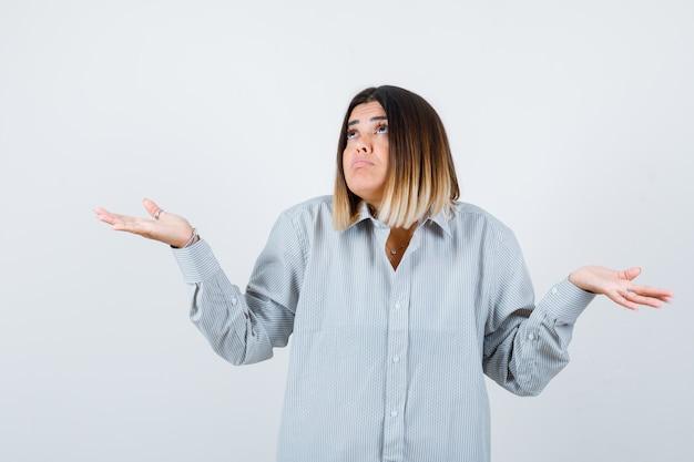 Młoda dama pokazująca bezradny gest w przewymiarowanej koszuli i wyglądająca na niezorientowaną. przedni widok.