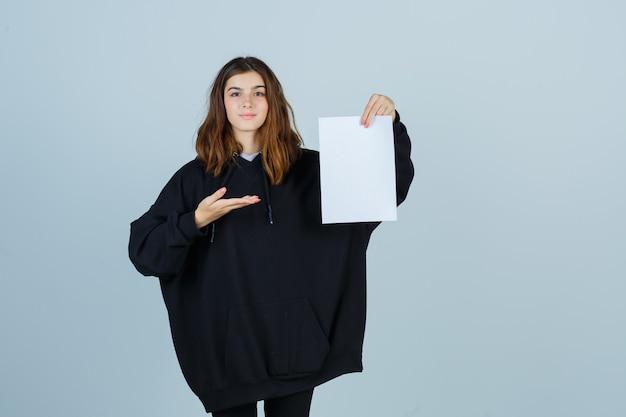 Młoda dama pokazująca coś, trzymając papier w obszernej bluzie z kapturem, spodniach i wyglądająca na pewną siebie, widok z przodu.