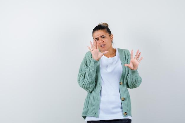 Młoda dama pokazująca dłonie w koszulce, kurtce i wyglądająca na pewną siebie