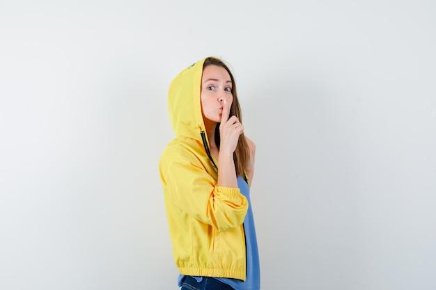 Młoda dama pokazująca gest ciszy w koszulce, kurtce i patrząc ostrożnie