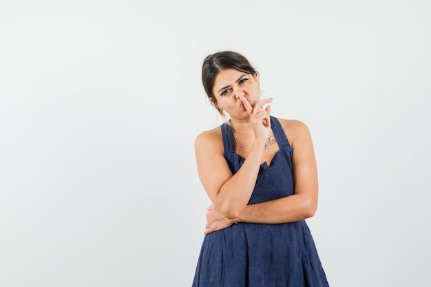 Młoda dama pokazująca gest ciszy w sukience i wyglądająca ostrożnie