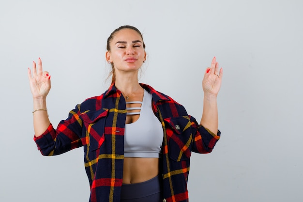 Młoda dama pokazująca gest medytacji w top, koszulę w kratę i wyglądającą na zrelaksowaną, widok z przodu.