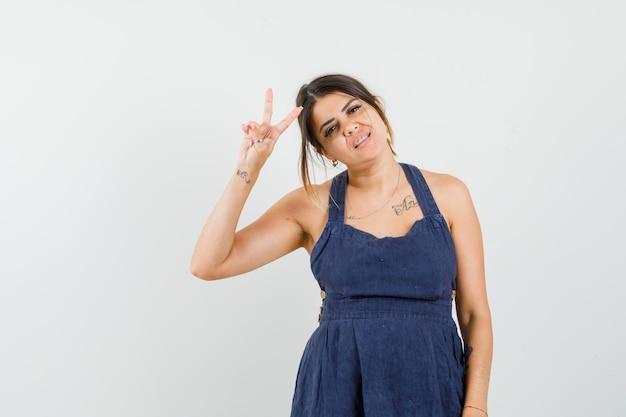 Młoda dama pokazująca gest zwycięstwa w sukience i wyglądająca pewnie
