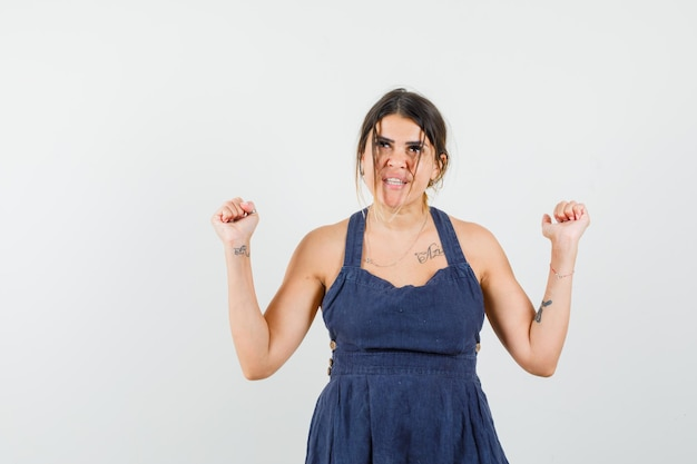 Młoda dama pokazująca gest zwycięzcy w sukience i wyglądająca na szczęśliwą
