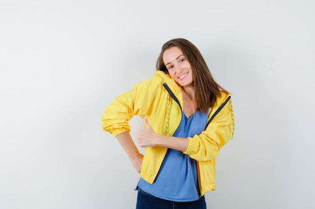 Młoda dama pokazująca kciuk w górę, wzruszając ramionami w koszulce, kurtce i wyglądając elegancko