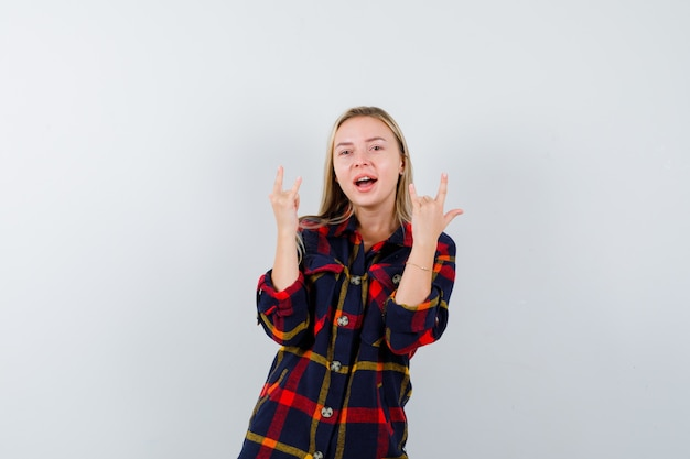 Młoda dama pokazująca kocham cię gest w kraciastej koszuli i wyglądająca energicznie, widok z przodu.