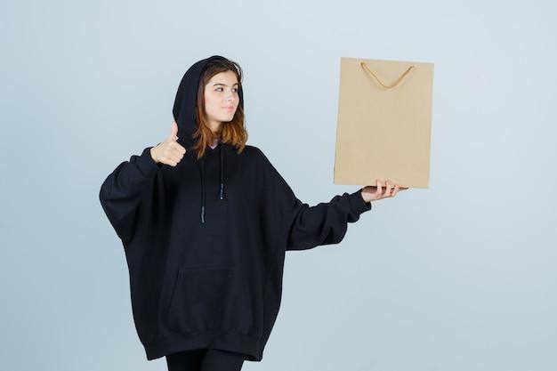 Młoda dama pokazująca łomot, trzymając paczkę w obszernej bluzie z kapturem, spodniach i wyglądająca błogo. przedni widok.