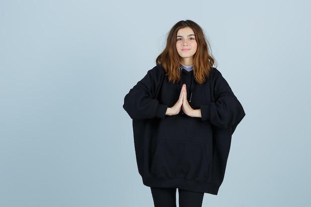 Młoda dama pokazująca namaste gest w obszernej bluzie z kapturem, spodniach i wyglądająca z nadzieją. przedni widok.