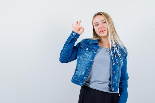 Młoda dama pokazująca ok gest w koszulce, dżinsowej kurtce, spódnicy i wyglądająca na szczęśliwą