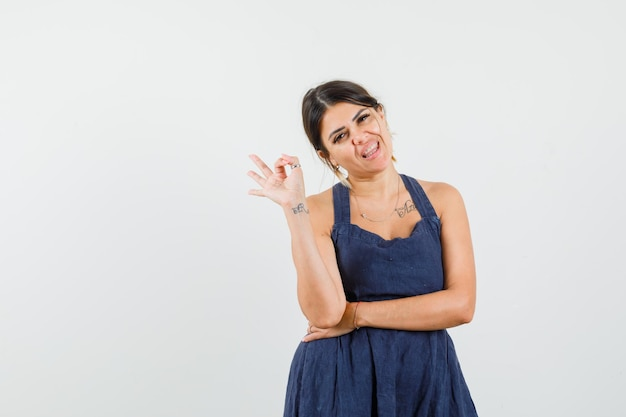 Młoda dama pokazująca ok gest w sukience i wyglądająca na zadowoloną