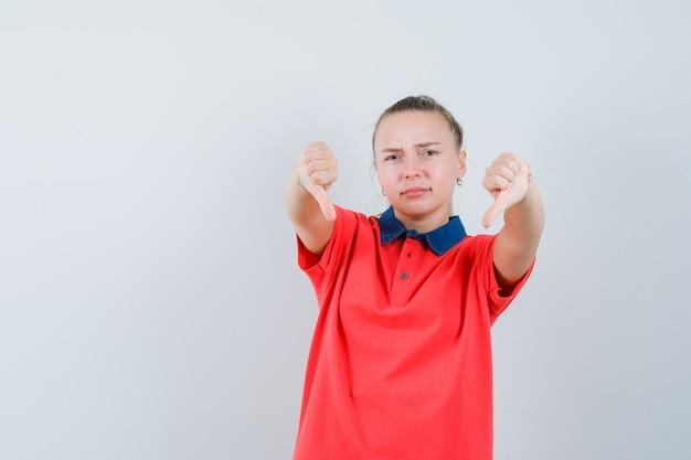Młoda dama pokazująca podwójne kciuki w koszulce i wyglądająca na niezadowoloną
