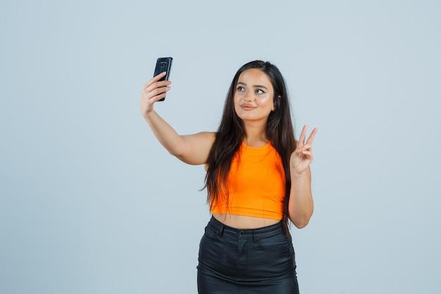 Młoda dama pokazująca znak zwycięstwa podczas robienia selfie w podkoszulku, mini spódniczce i atrakcyjnym wyglądzie. przedni widok.