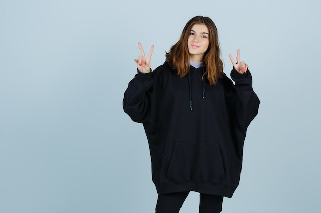 Młoda dama pokazująca znak zwycięstwa w obszernej bluzie z kapturem, spodniach i wyglądająca na szczęśliwą w widoku z przodu.