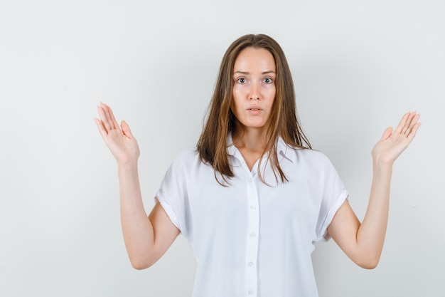 Młoda dama pokazuje bezradny gest w białej bluzce i wygląda na zdezorientowanego