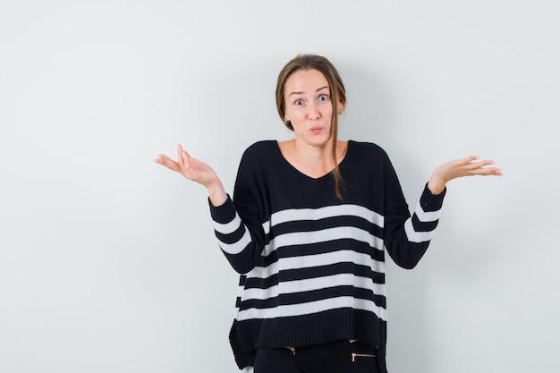 Młoda dama pokazuje bezradny gest w przypadkowej koszuli i wygląda na zdezorientowanego