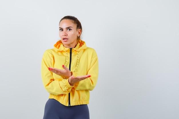 Młoda dama pokazuje bezradny gest w żółtej kurtce i wygląda na przestraszoną. przedni widok.