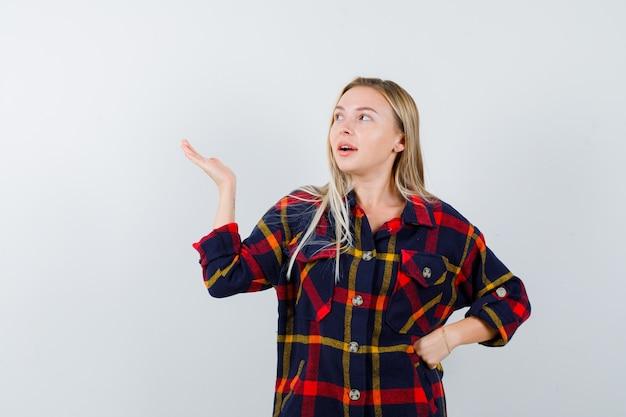 Młoda dama pokazuje coś, trzymając rękę na talii w kraciastej koszuli i wyglądająca na pewną siebie. przedni widok.