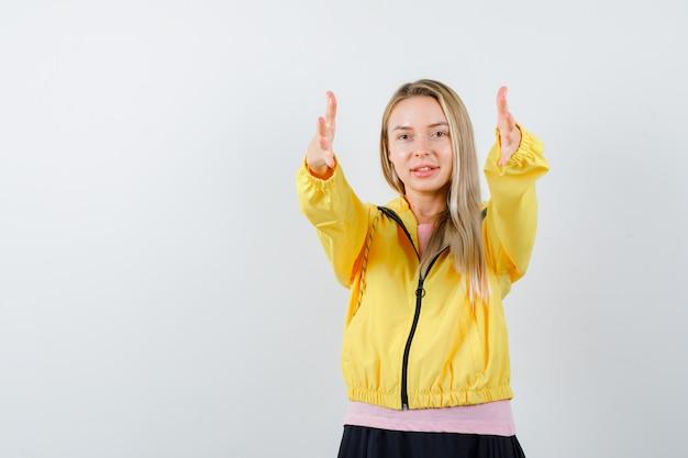 Młoda dama pokazuje dając gest w koszulce, kurtce i patrząc pewnie