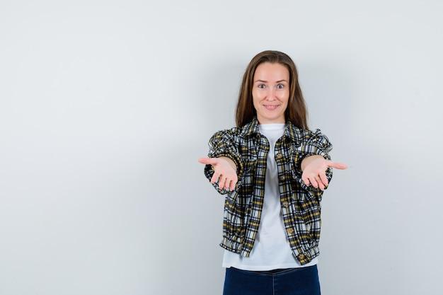 Młoda dama pokazuje dając gest w t-shirt, kurtkę, dżinsy i ładnie wyglądający. przedni widok.