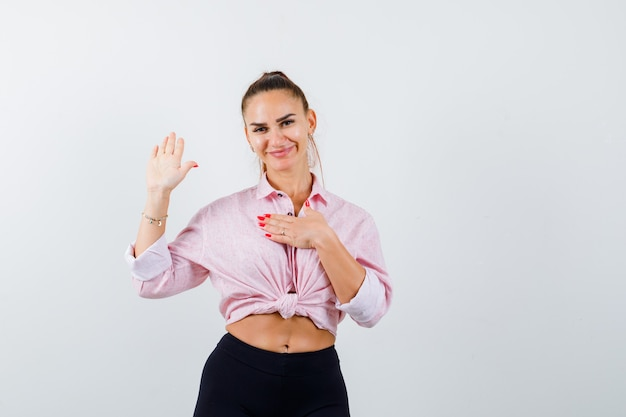 Młoda dama pokazuje dłoń, trzymając rękę na klatce piersiowej w koszuli, spodniach i patrząc wesoło, widok z przodu.