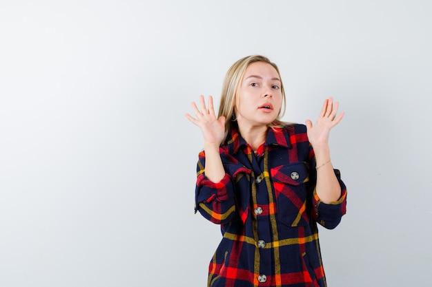 Młoda dama pokazuje dłonie w geście kapitulacji w koszuli w kratę i wygląda na zdziwioną, widok z przodu.