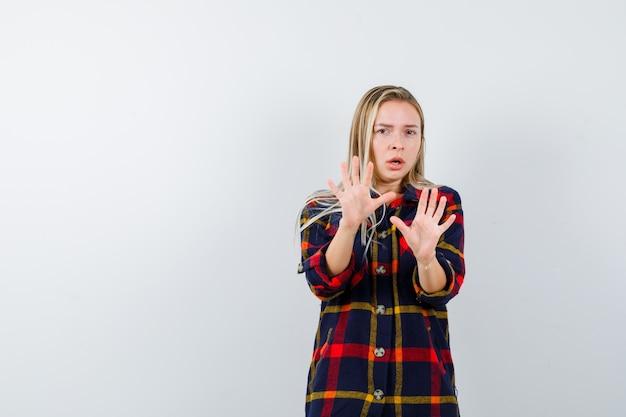Młoda dama pokazuje dłonie w geście kapitulacji w koszuli w kratkę i wygląda na przestraszoną, widok z przodu.