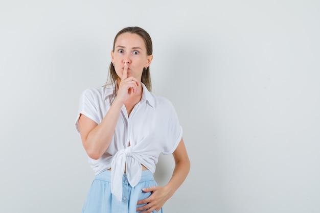 Młoda dama pokazuje gest ciszy w bluzce i spódnicy i wygląda poważnie