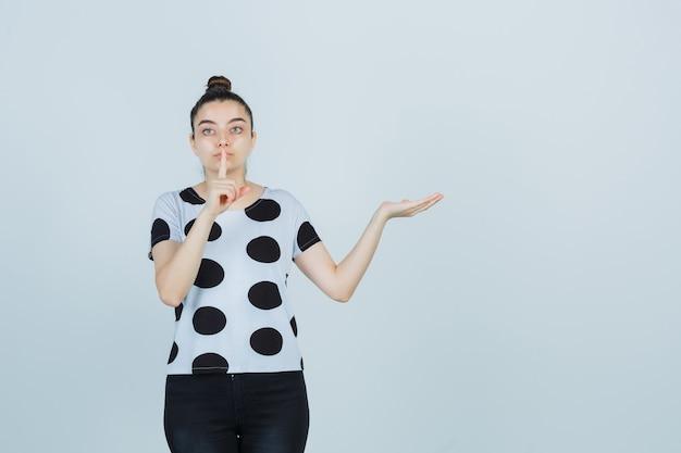 Młoda dama pokazuje gest ciszy w koszulce, dżinsach i wygląda poważnie. przedni widok.