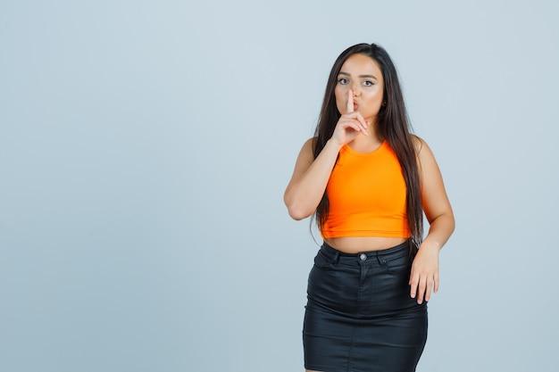 Młoda dama pokazuje gest ciszy w podkoszulku, mini spódniczce i wygląda pewnie. przedni widok.