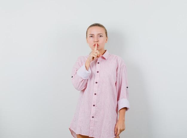Młoda dama pokazuje gest ciszy w różowej koszuli i wygląda elegancko