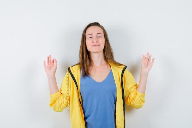 Młoda dama pokazuje gest medytacji w koszulce i wygląda na zrelaksowaną. przedni widok.