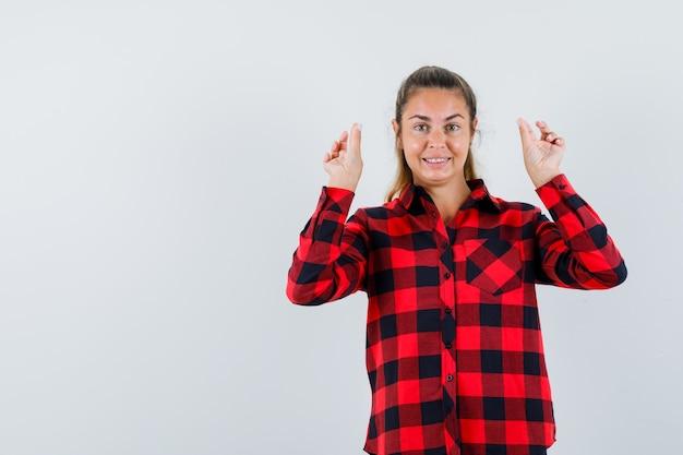 Młoda dama pokazuje gest medytacji w kraciastej koszuli i wygląda wesoło