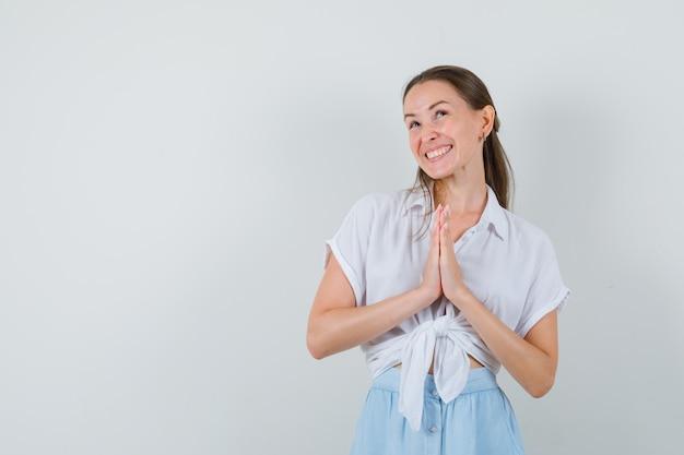 Młoda dama pokazuje gest namaste w bluzce i spódnicy i wygląda na szczęśliwego
