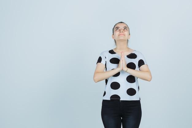 Młoda dama pokazuje gest namaste w koszulce, dżinsach i wygląda z nadzieją. przedni widok.