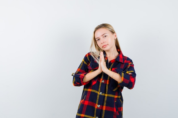 Młoda dama pokazuje gest namaste w kraciastej koszuli i wygląda z nadzieją. przedni widok.