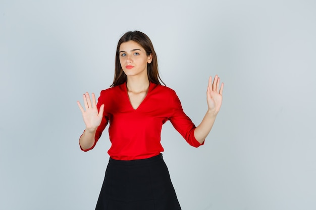 Młoda dama pokazuje gest ograniczenia w czerwonej bluzce, czarnej spódnicy i wygląda poważnie