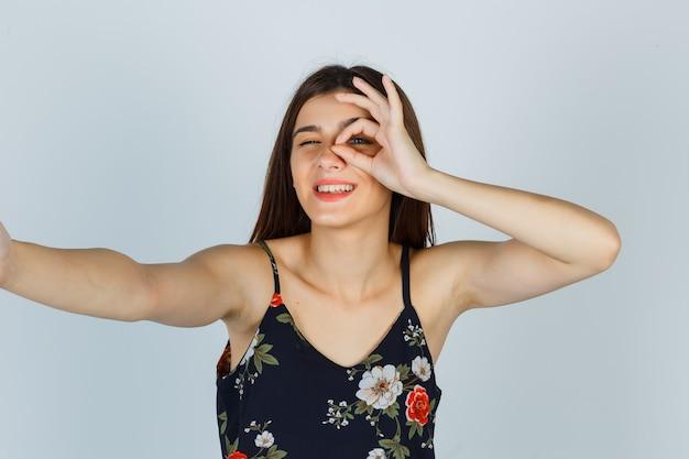 Młoda dama pokazuje gest ok w kwiatowy top i wygląda wesoło