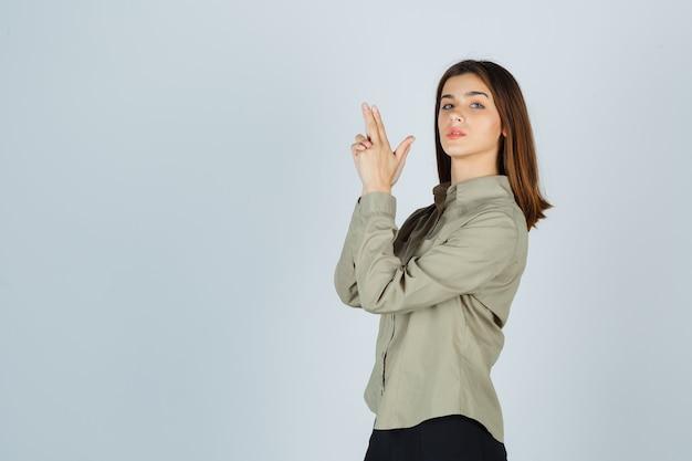 Młoda dama pokazuje gest pistoletu w koszuli, spódnicy i wygląda poważnie.