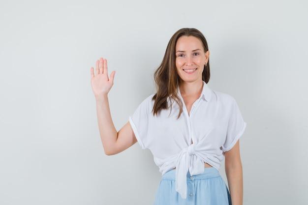 Młoda dama pokazuje gest powitania w bluzce i spódnicy i szuka zadowolony