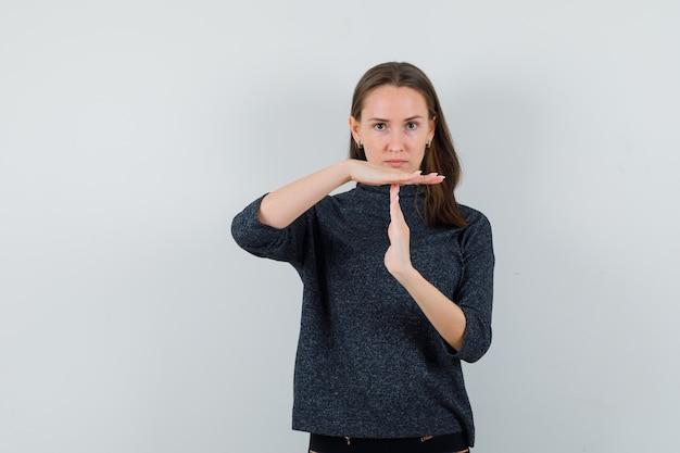 Młoda dama pokazuje gest przerwy w koszuli i wygląda poważnie