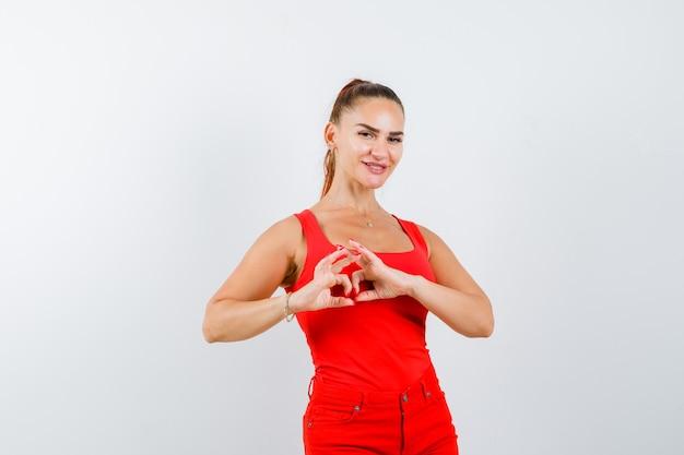 Młoda dama pokazuje gest serca w czerwonym podkoszulku, czerwonych spodniach i ładnie wygląda. przedni widok.