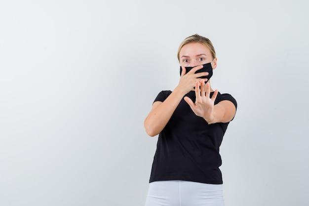 Młoda dama pokazuje gest stop, trzymając dłoń na ustach w czarnej koszulce, masce i przestraszony, widok z przodu.