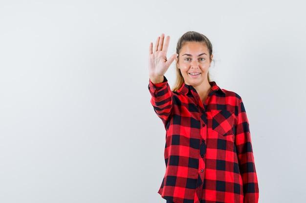 Młoda dama pokazuje gest stop w koszuli w kratkę i wygląda zamyślona