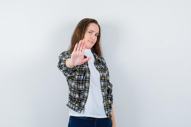 Młoda dama pokazuje gest stopu w koszulce, kurtce i wygląda na znudzoną, widok z przodu.