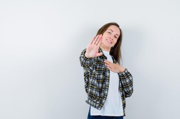 Młoda dama pokazuje gest stopu w koszulce, kurtce i wygląda pewnie. przedni widok.
