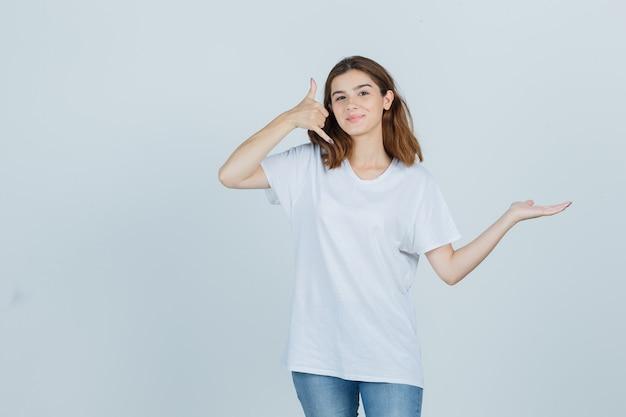 Młoda dama pokazuje gest telefonu, udając, że trzyma coś w koszulce, dżinsach i wygląda na pewną siebie, widok z przodu.