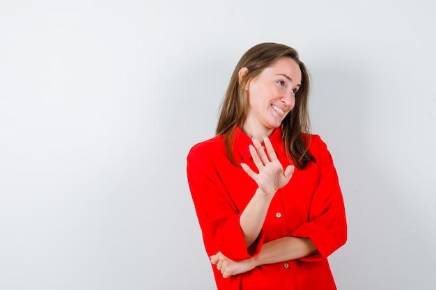 Młoda dama pokazuje gest zatrzymania w czerwonej bluzce i wygląda na zawstydzoną. przedni widok.