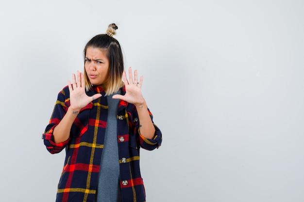 Młoda dama pokazuje gest zatrzymania w dorywczo kraciastej koszuli i wygląda na niezadowoloną, widok z przodu.
